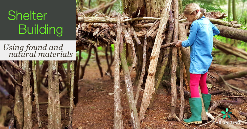 Two children building a shelter from wood branches